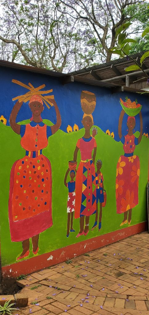 Mural showing women and girls carrying loads on their heads.
